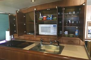 61' Buddy Davis 61 Sportfish 1989 mirrored doors open above Galley sink